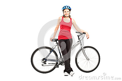 Female biker with helmet posing next to a mountain bike