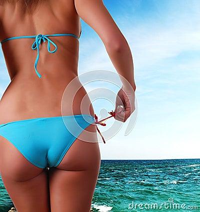 Female body in swimwear and sea