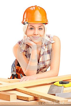 Female carpenter with helmet posing at workplace