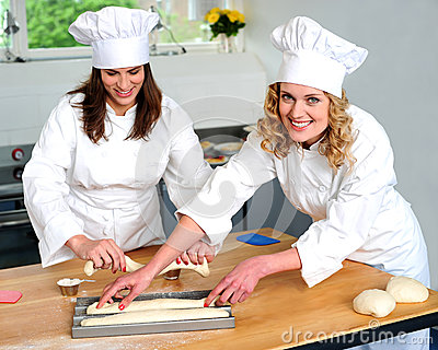 Female chef arranging prepared dough