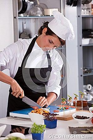 Female chef cutting an onion