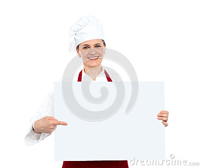 Female chef pointing towards blank whiteboard