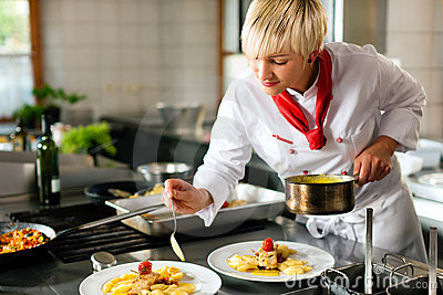 Female chef in a restaurant or hotel kitchen cooki