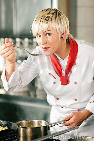 Female Chef in a restaurant kitchen tasting