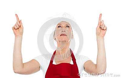 Female chef in uniform pointing upwards