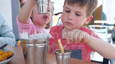 Female child gives male child sauce for French fries, Boy and girl are having an appetizing dinner in restaurant. Beautiful brother and sister make snack by stock footage