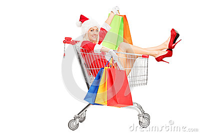 Female in christmas costume into a push cart