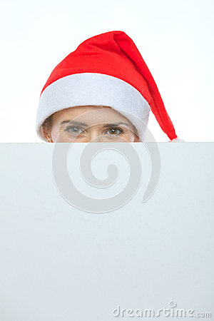 Female in Christmas hat hiding behind billboard