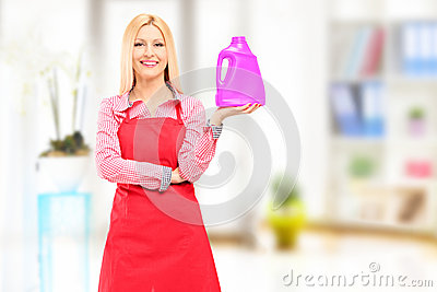 Female cleaner holding a bottle of detergent and posing at home