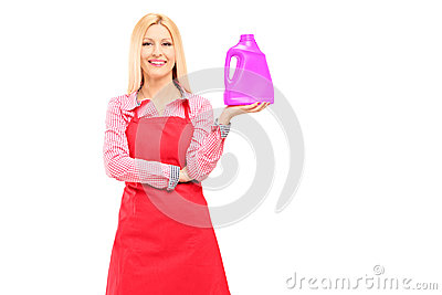 Female cleaner holding a bottle of detergent and posing