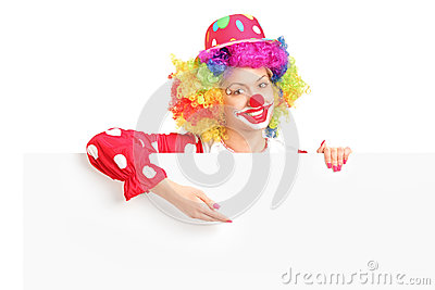 Female clown posing behind white panel