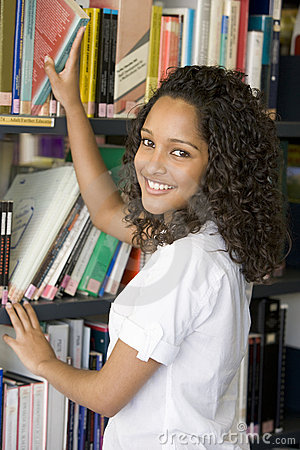 Free Female College Student Reaching For A Library Book Royalty Free Stock Photo - 5949575