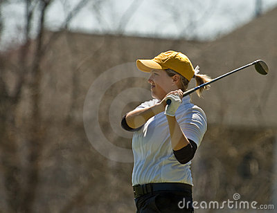 Female collegiate golfer swinging golf club