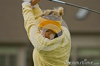 Female collegiate golfer swinging golf club