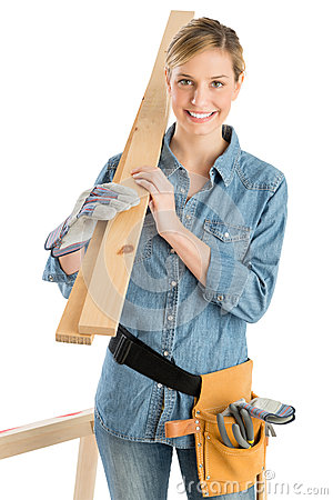Female Construction Worker Carrying Wooden Plank On Shoulder