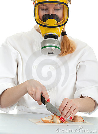Female cook cutting onion in gas mask