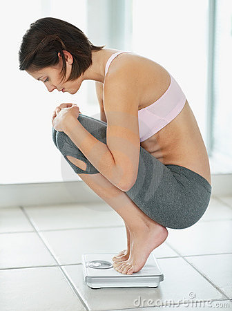 Female crouching on a weighing scale