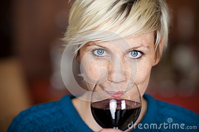 Female Customer Drinking Red Wine In Restaurant