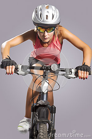 Female cycling athlete riding mountain bike and equipped with pr