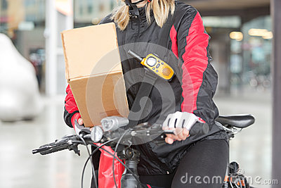 Female Cyclist With Cardboard Box And Courier Bag