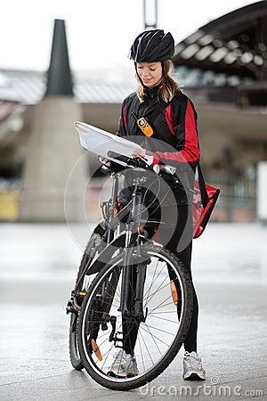 Female Cyclist With Courier Bag And Package On