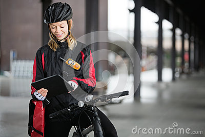 Female Cyclist With Courier Bag Using Digital