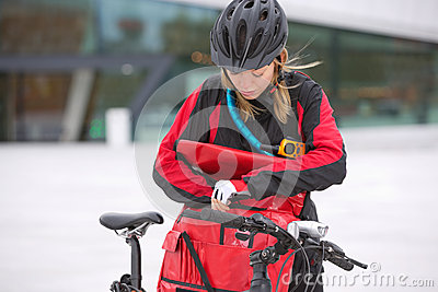 Female Cyclist Looking Through Courier Delivery