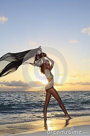 Female dancer standing by the ocean