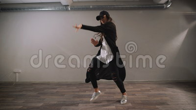 Female dancer in white shirt, black trousers and black cap showing modern jazz-funk dancing in classroom with mirrors. Female dancer dressed in white shirt stock footage