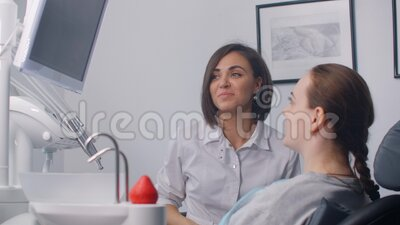 A female dentist shows an MRI image on the screen and an x-ray of the patient`s teeth. Discussion of the treatment plan. And healthy smile stock footage