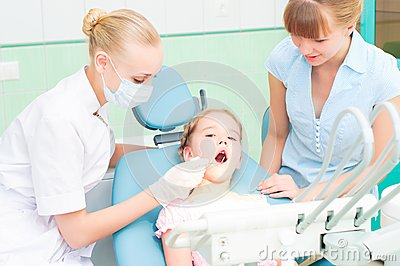 Female dentists examines a child