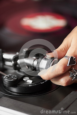 Female DJ adjusting turntable tonearm