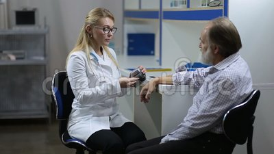 Cardiologist measuring patient`s blood pressure stock video