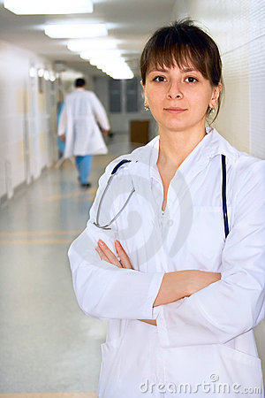 Female doctor in corridor under lamps