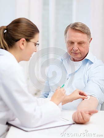 Female doctor doing injection to old man