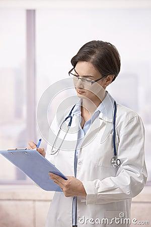 Female doctor doing paperwork in hospital