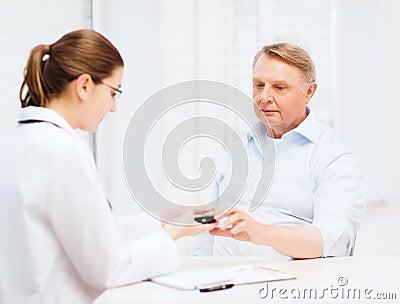 Female doctor or nurse measuring blood sugar value