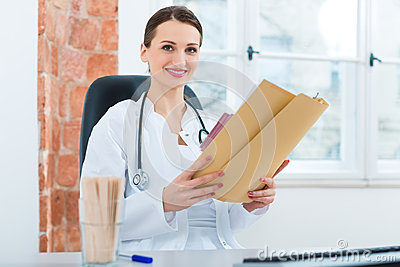 Female doctor reading in document