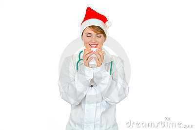 Female doctor in Santa hat enjoying cup of hot cof