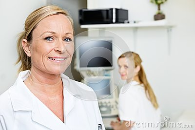 Female Doctor Smiling With Colleague In Background
