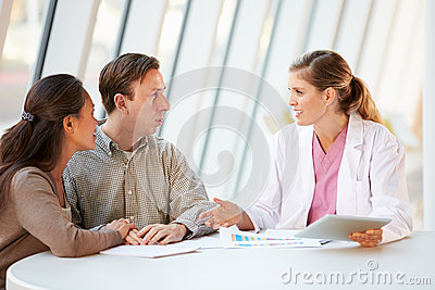Female Doctor Using Digital Tablet Talking With Patients