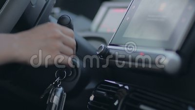 Female driver hand putting ignition key to keyhole stock video