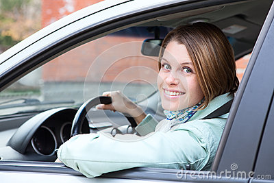 Female driver looking back from car
