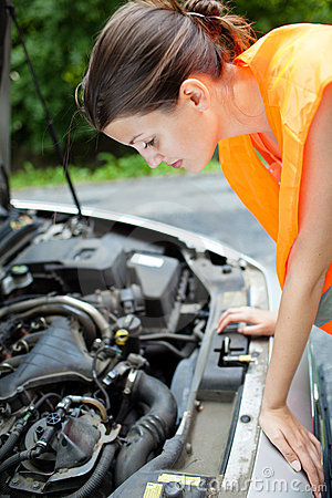 Female driver over the engine of her broken down c