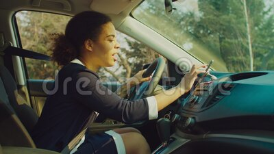 Female driver using smartphone for gps navigation in car. Positive beautiful african female driver in stylish clothes using smart phone for gps navigation in car stock footage