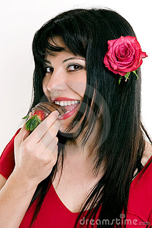 Female eating fresh strawberries in chocolate