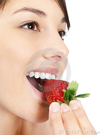 Female eating a fresh strawberry against white