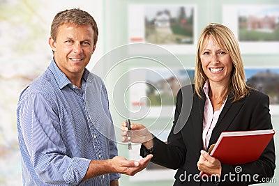 Female Estate Handing Over Keys Of New Home