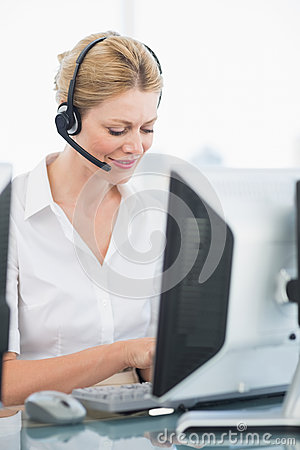 Female executive with headset using computer at desk