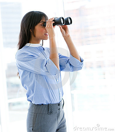 Female executive looking through binoculars